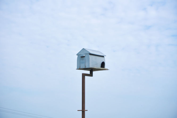 Low angle view of birdhouse on wooden post against sky