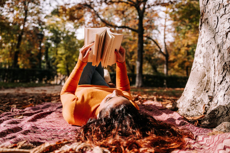 Woman reading book while lying at park during autumn