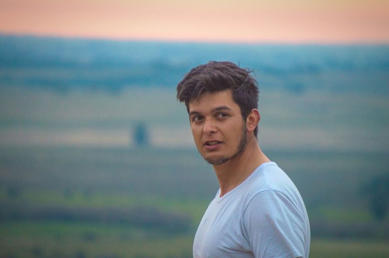Handsome young man looking away while standing on landscape against sky during sunset