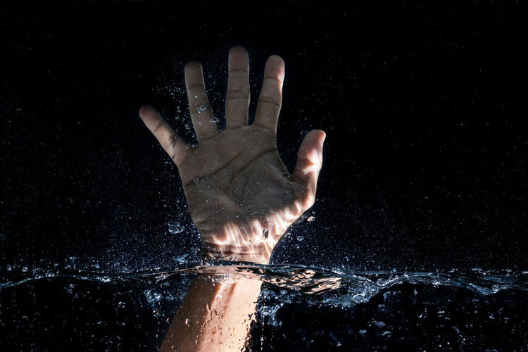 Close-up of hand touching water against black background