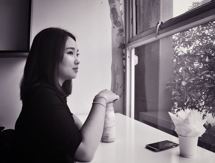 Side view of thoughtful woman having drink at cafe
