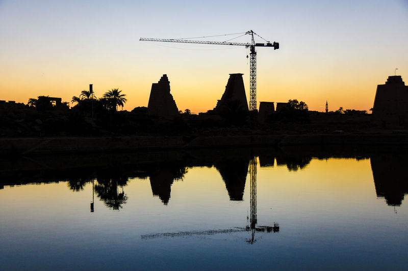 Construction EyeEm Best Shots Karnak Temple Karnak Temple Complex Middle East Ruins Sightseeing Sunset Silhouettes Ancient Architecture Architecture Beauty In Nature Building Exterior Crane Reflection Restoring Sacred Lake Sights Silhouette Sunrise_sunsets_aroundworld Sunset Symmetry Travel Destinations Water