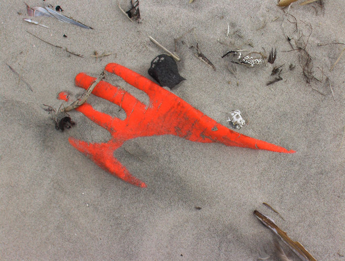 Directly above shot of abandoned orange glove on sandy beach