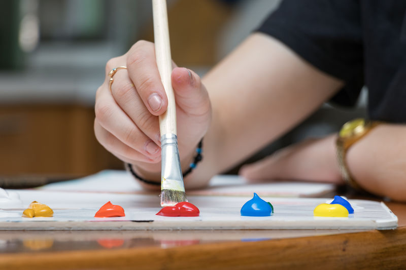 Close-up of a female teenage hand mixing colors with a paintbrush on a color palette