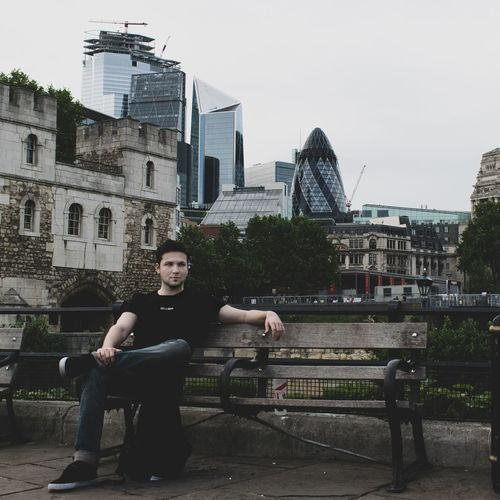 Portrait of young man against buildings in city