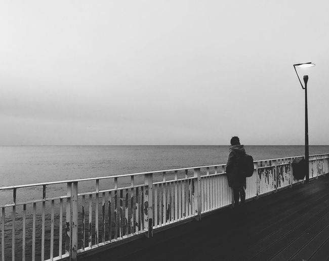 Rear view of man standing on railing against sea