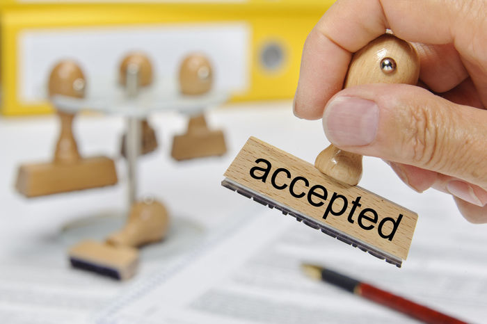 accepted printed on rubber stamp holding in hand Accepted Application Assessment Authority Office Accept Acceptance Agree Agreement Allow Allowance AllOwed Approval Approved Confirm Confirmation Document Hand Holding Human Hand Passed Permit Permitted Stamp Text