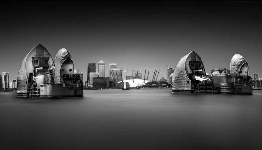A long exposure taken in the east end of London, near Greenwhich of the Thames Barrier. Architecture Arts Culture And Entertainment Business Business Finance And Industry Canary Whrarf City Cityscape East End Ferris Wheel Harbor Horizontal London Modern Night No People Outdoors Reflection Sky Skyscraper Thames Barrier Travel Destinations Urban Skyline
