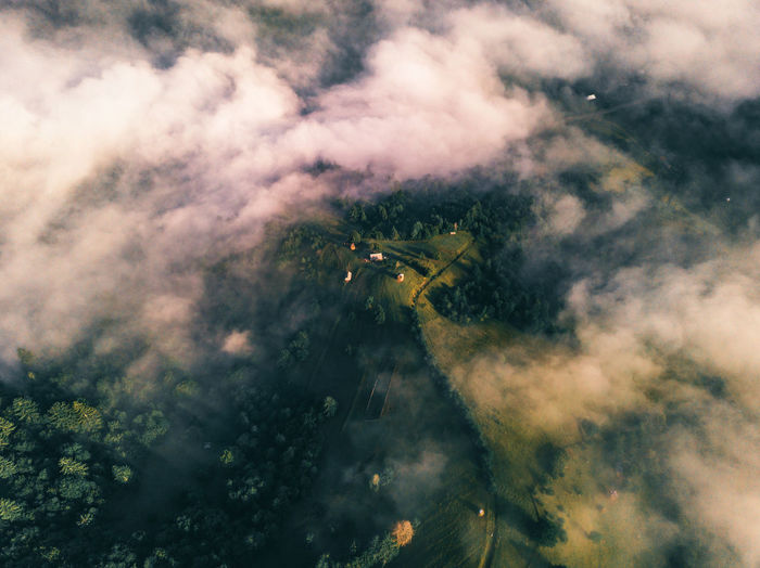 Aerial view of the small settlement surrounded by mountains. drone flight through the clouds