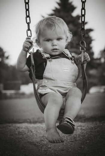 Full length portrait of baby boy on swing at playground