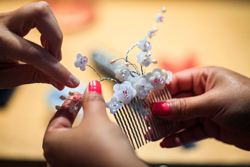 Close-up of hands holding decorative comb
