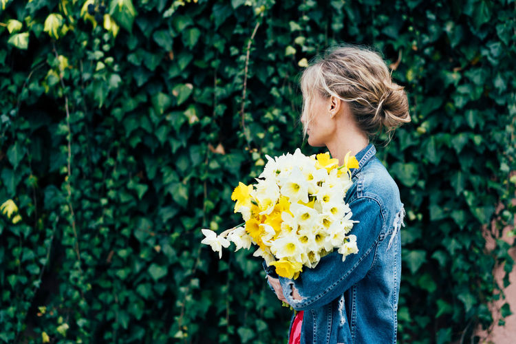 Side view of woman holding flowers while standing against plants