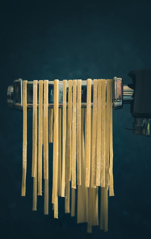 fresh homemade pasta hanging over the pasta machine | daylight foodphotography martin willmann Black Background Homemade Homemade Food Homemade Pasta Kenwood Close-up Dark Background Dark Mood Daylight Photography Focus On Foreground Food Photography Foodphotography Fresh Group Of Objects In A Row Indoors  Italien Food Large Group Of Objects Moody Nikonphotography No People Pasta Pasta Machine Side By Side Still Life