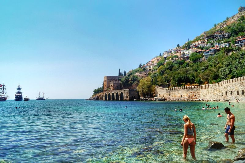Going For A Swim Water Fun Sunny Day Fortress Wall of the Old Harbour of Alanya/Turkey and Pirate Ships In The Background Clear Water Bay Where The Locals Go For A Swim Blond Girl In The Foreground Showcase July