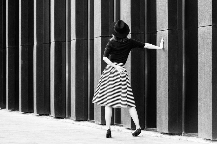 Rear view of a woman walking by the wall