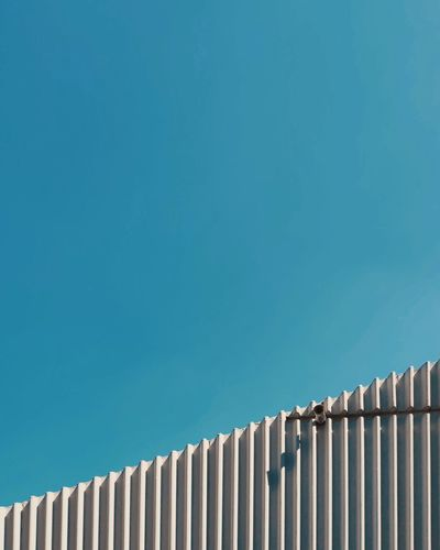 Low angle view of cctv camera on a wall against clear blue sky