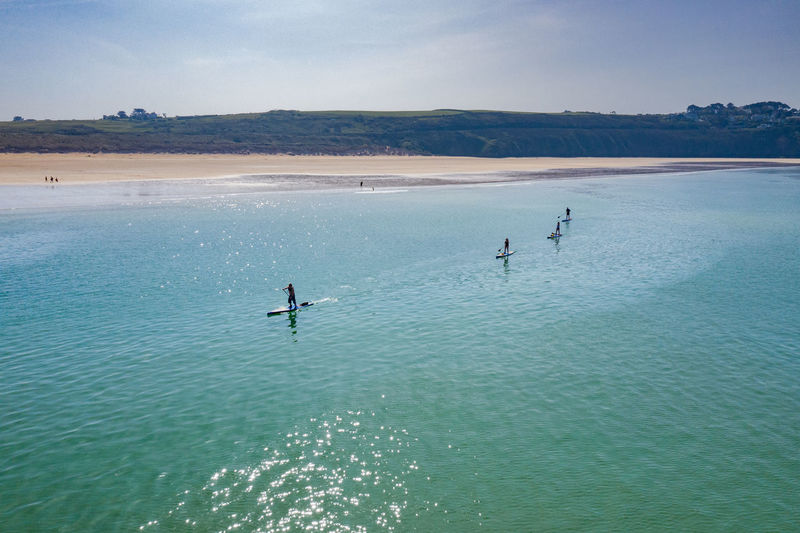 People paddleboarding in sea against sky