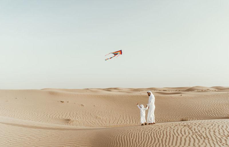 Full length of father with son flying kite in desert