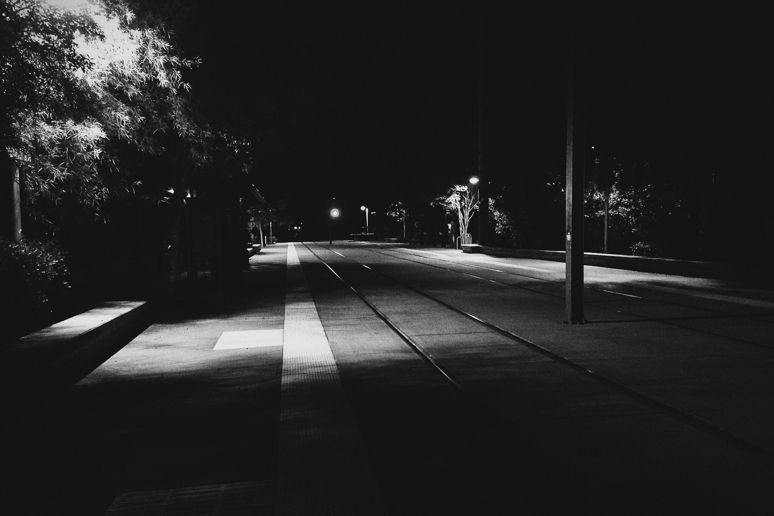 night, illuminated, street light, the way forward, tree, built structure, architecture, street, building exterior, transportation, lighting equipment, road, empty, dark, clear sky, city, diminishing perspective, outdoors, no people, vanishing point