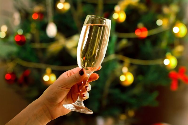 Cropped Image Of Hand Holding Champagne Flute Against Christmas Tree