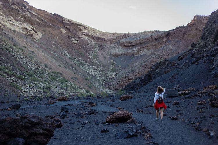 Rear view of woman walking on rock against sky