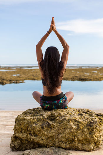 Rear View Of Young Woman Doing Yoga On Beach