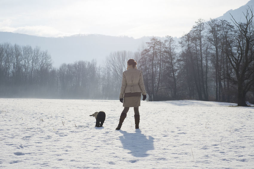Woman walking with her dog in the winter nature in a sunny day in Switzerland. Adults Only Animal Themes Cold Temperature Day Dog Domestic Animals Freedom Mountain Nature One Animal One Person One Woman Only Outdoors Pets Playing With The Animals Skirt Sky Snow Sunshine Swiss Alps Tree Walking Warm Clothing Winter Woman