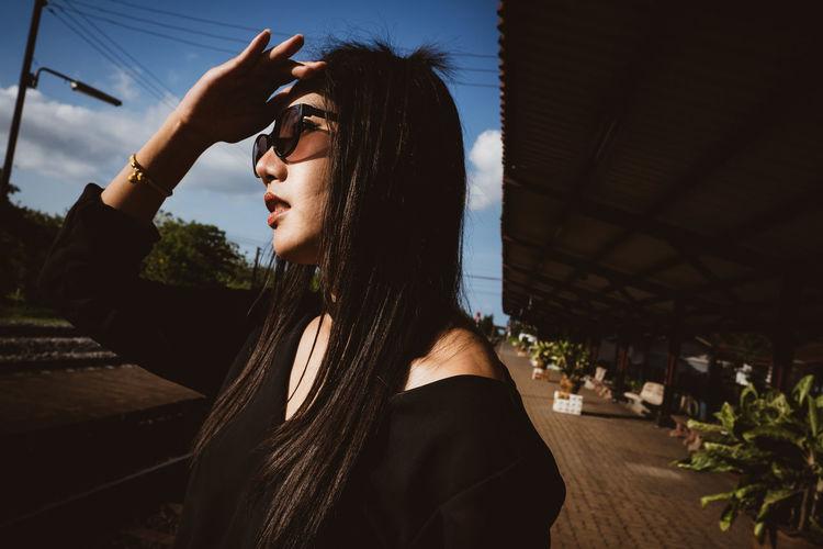 Woman shielding eyes in city