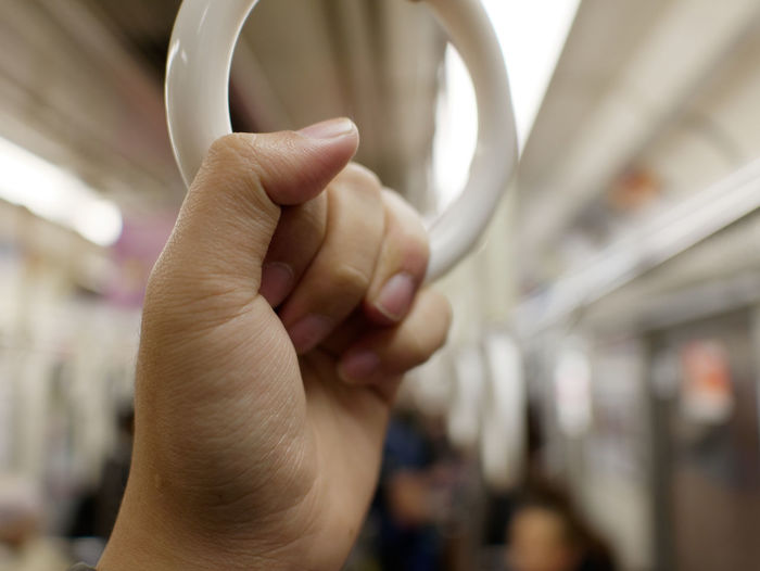 Cropped Hand Holding Handle In Illuminated Train