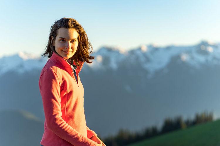 Portrait of woman standing against mountain range against sky