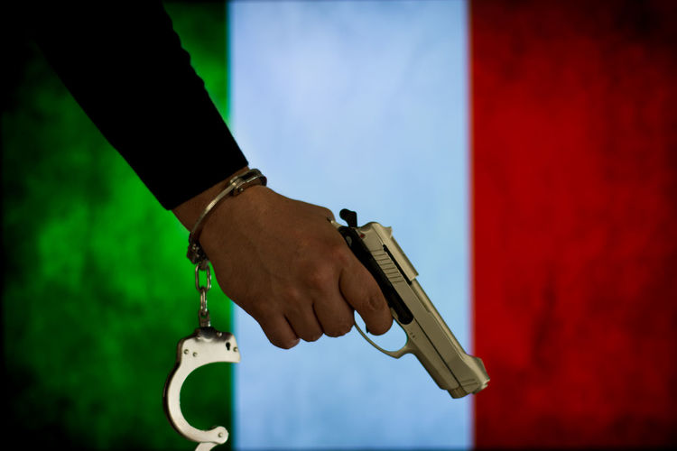 Cropped hand of male criminal holding gun against italian flag
