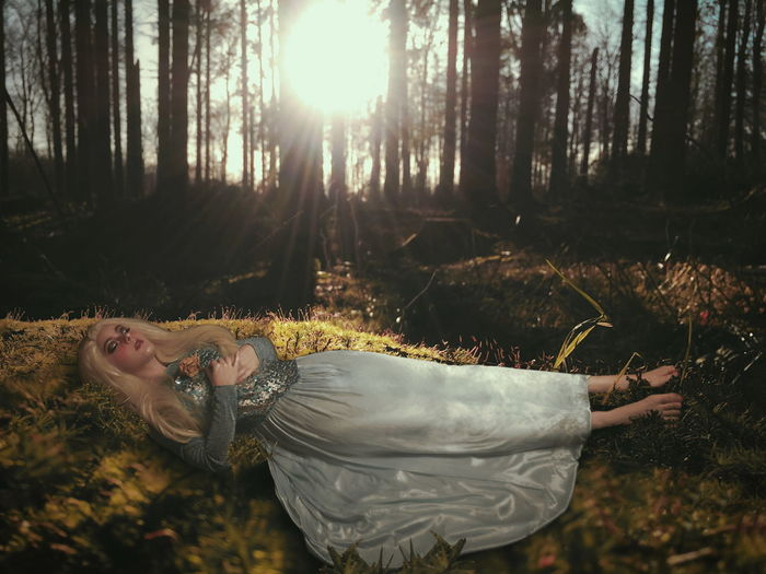 Woman lying down on land in forest