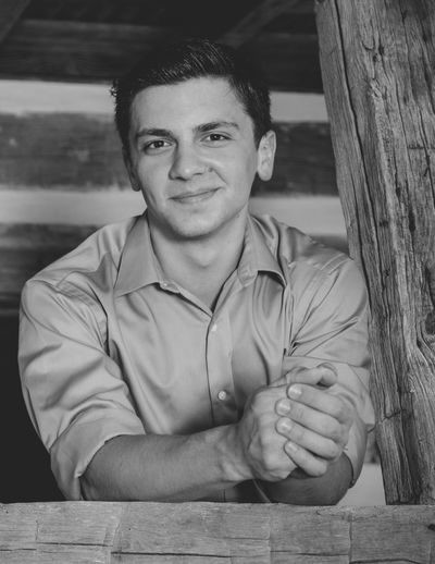 Portrait Of Smiling Young Man Standing In Log Cabin