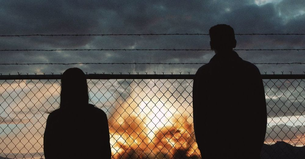 Rear view of silhouette man standing by fence against sky during sunset