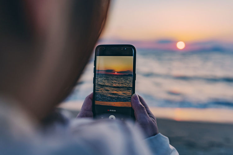Man Photographing Sea Through Smart Phone During Sunset