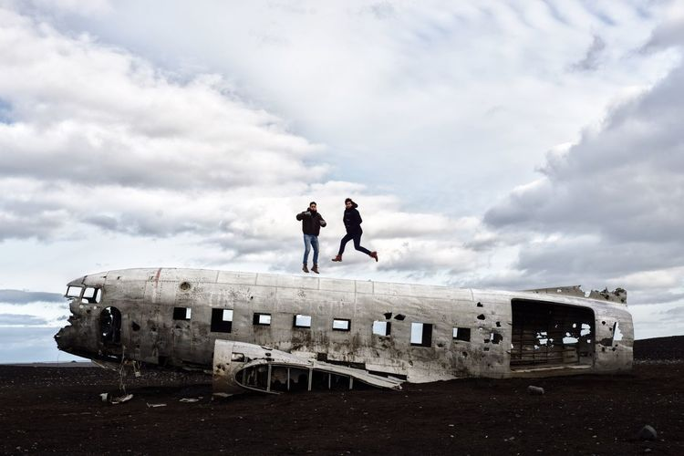 People jumping over abandoned airplane against cloudy sky