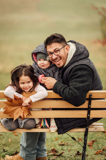 Portrait of father with kids sitting on bench outdoors