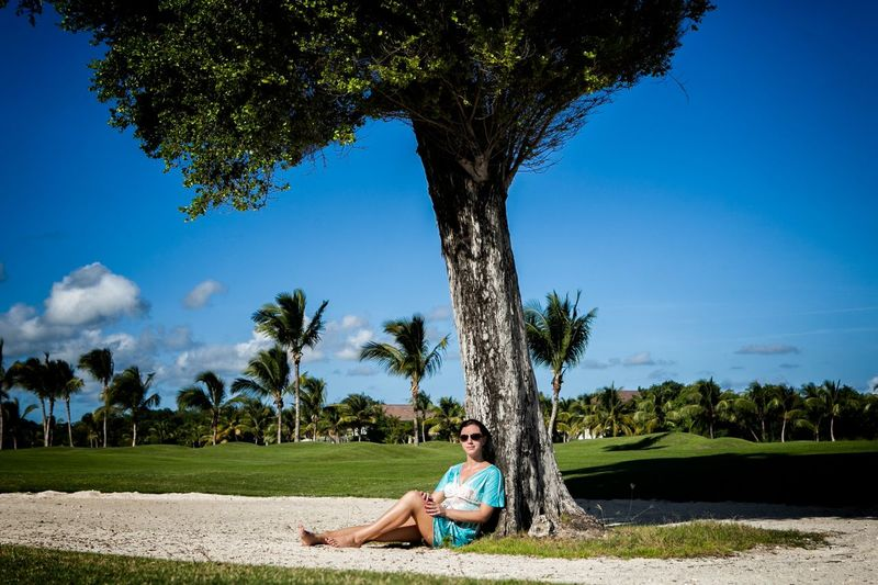 Portrait Of Woman In Sunglasses Leaning On Tree