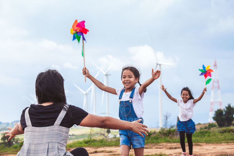 Mother and daughters playing with pinwheel toys on land with windmills in background