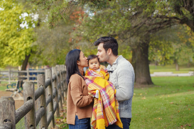 Couple standing with baby at park