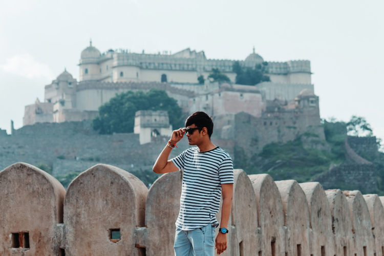 Man wearing sunglasses standing against fort