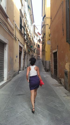 Rear view of woman walking on alley amidst buildings