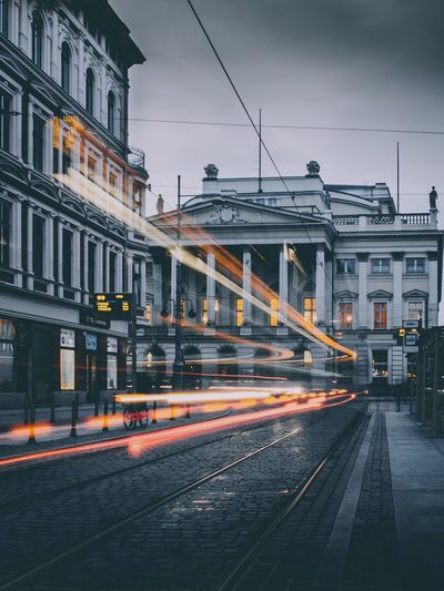 Light trail on street against buildings in city at twilight