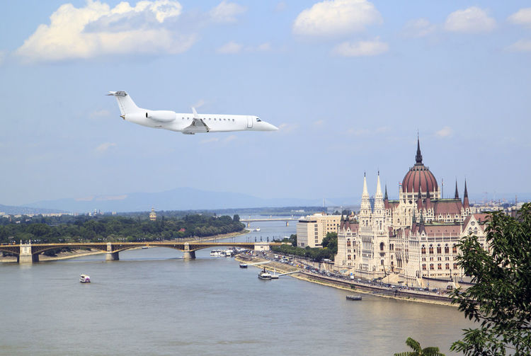 Airplane flying over river with city in background