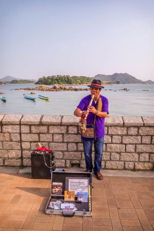 The Woodwinder Art Boats Evening Hat HongKong Instruments Leisure Activity Mountains Music Musician Outdoors Pavement Performance Pipe Purple Saikung Seafront Sky Speaker Tophat Wall Woodwind
