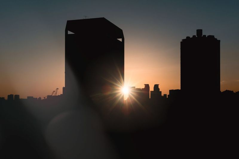 Sunlight streaming through silhouette buildings against sky during sunset