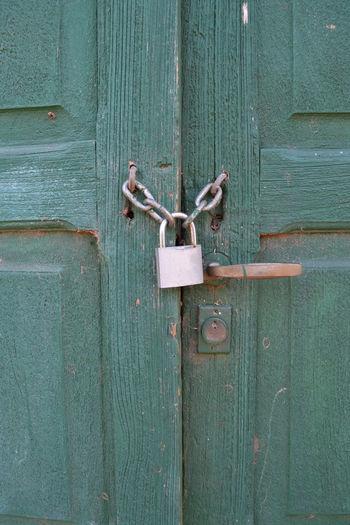 Close-up of padlocks on green wooden door