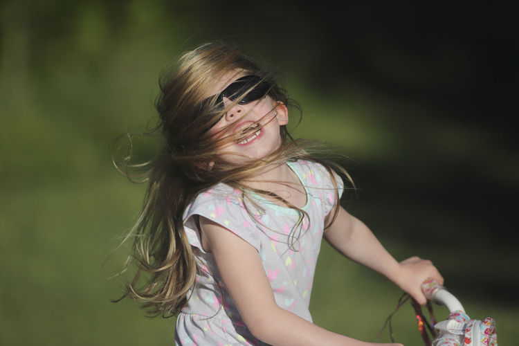Bicycle Blond Hair Casual Clothing Childhood Day Elementary Age Focus On Foreground Girls Hair Happiness Happiness Joy Laughing Love One Person Outdoors People Shaking Head Smiling Spring Summer Sunglasses Wind Sommergefühle