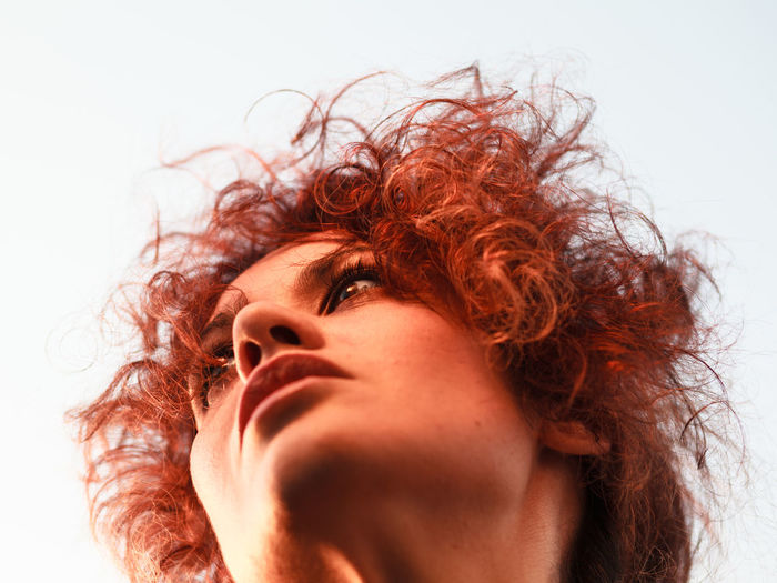 Low Angle View Of Thoughtful Woman Looking Away Against Sky