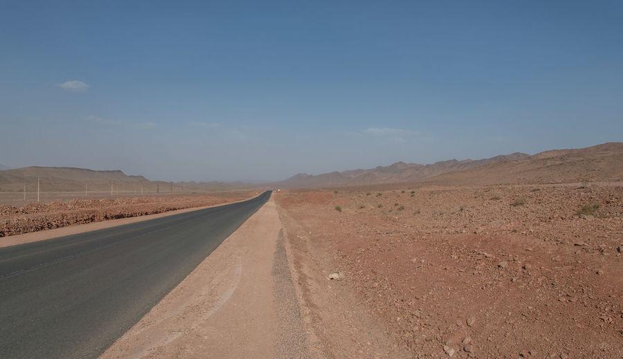 Road leading towards desert against sky